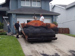 Owner Kenny Withrow performing asphalt pavement services in Anchorage, Alaska