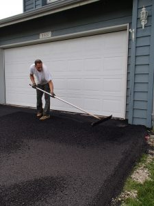 laying down asphalt for a new driveway in Anchorage, Alaska